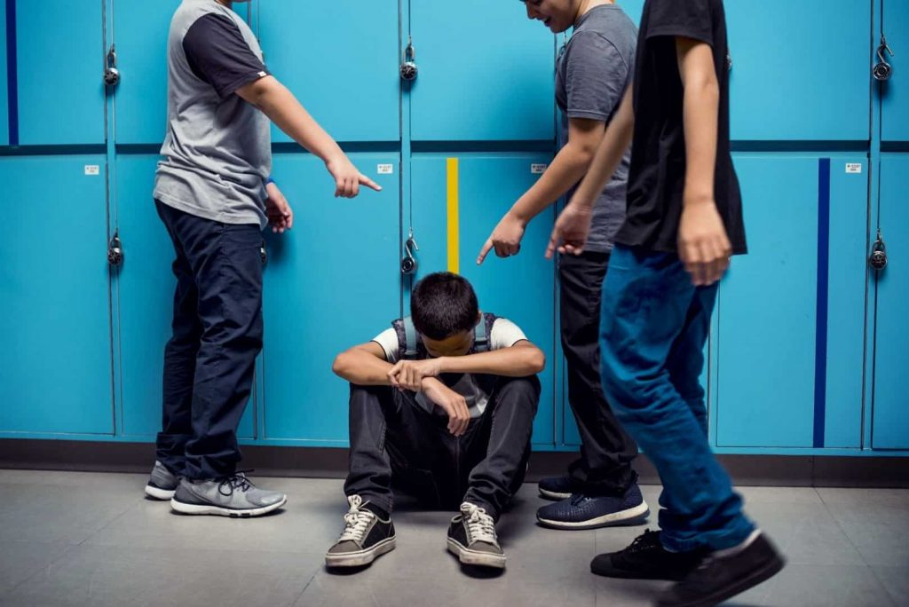 Three older boys pointing on the younger boy, sitting on the floor and hiding his face