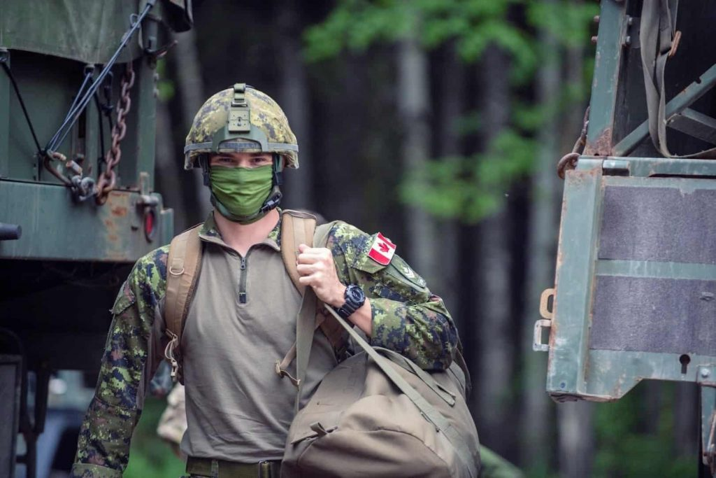 A soldier of the Department of National Defence of Canada is holding his backpack